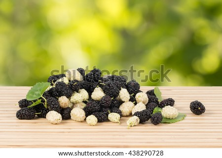 Closeup heap of ripe white and black mulberries with green leaves on table on green leaves background. Horizontal - stock photo