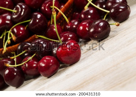 Closeup horizontal angled view of black cherries spilled out of basket onto faded white boards - stock photo