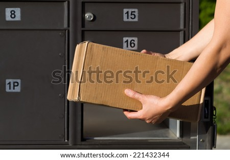 Closeup horizontal front view of female hands putting package into postal mailbox with green grass and sidewalk in background  - stock photo