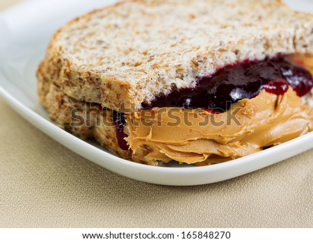Closeup horizontal photo of a peanut butter and jelly sandwich cut in half, inside white plate on textured table cloth underneath