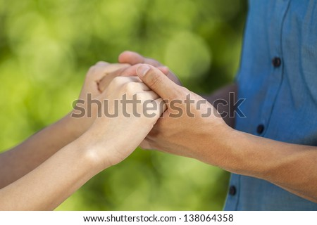 closeup horizontal photo of a young adult couple holding hands with blurred out green woods in background - stock photo