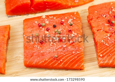 Closeup horizontal photo of dried red peppercorns and sea salt on top of fresh Wild Red Salmon pieces with natural bamboo cutting board underneath  - stock photo