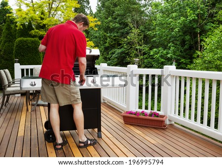 Closeup horizontal photo of mature man working on BBQ grill on open cedar patio with seasonal trees in full bloom in background  - stock photo