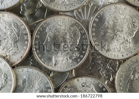 Closeup horizontal photo of several United States Silver Dollars, obverse side up, piled up - stock photo