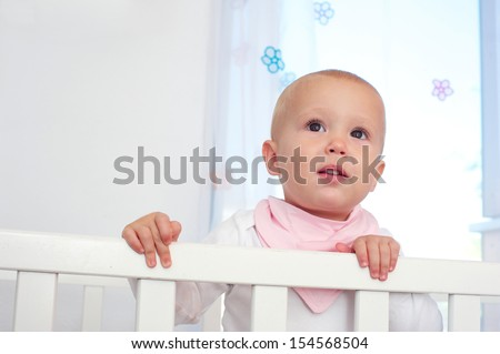Closeup horizontal portrait of a cute baby in crib