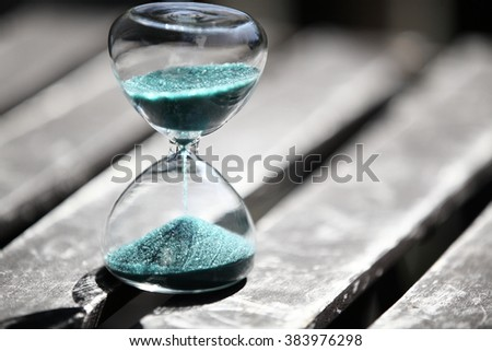 Closeup hourglass clock on wooden table background - stock photo