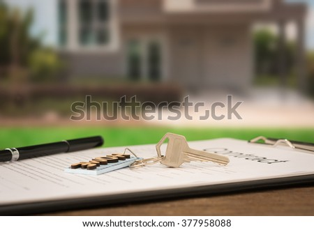 closeup house key on contract document with house key in house background. - stock photo