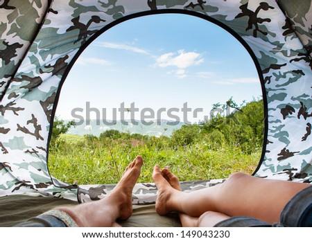 Closeup image couple legs lying together near open door tourist tent - stock photo