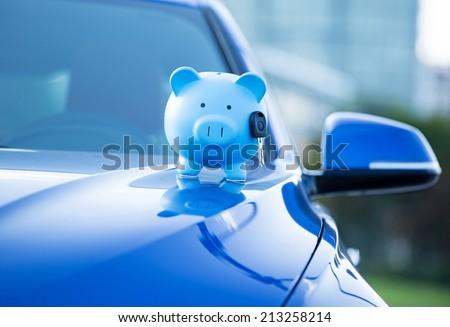 Closeup image new car with piggy bank, key on hood isolated outside corporate building. Dealership offering credit line finance services. Lease automobile purchase financing concept. Financial success - stock photo