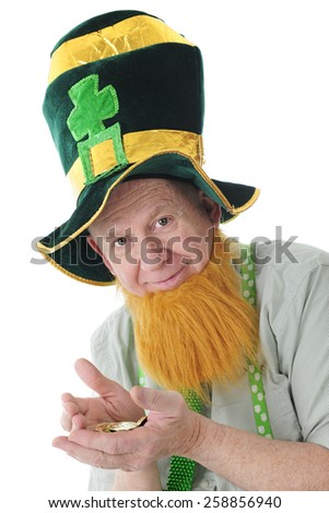Closeup image of a bearded Irish man in a tall Irish hat happy with his hands full of Irish gold.  On a white background.