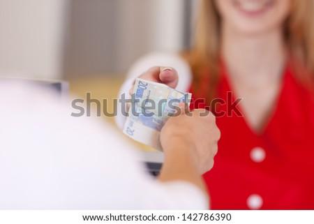 Closeup image of a customer handing 20 Euros at the cash counter. - stock photo