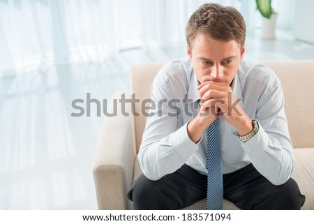 Closeup image of a despair business patient waiting for psychologist for session  - stock photo