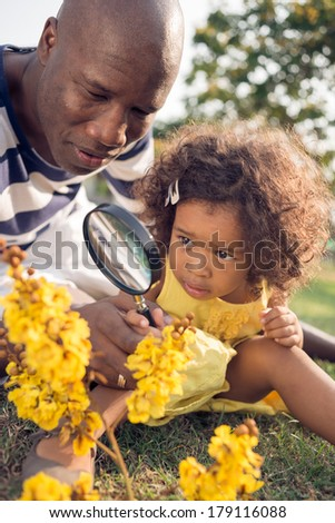 Closeup image of a father looking at the yellow flowers through the magnifier with his little daughter on the foreground  - stock photo