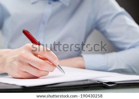 Closeup image of a female professional signing a document with a pen.