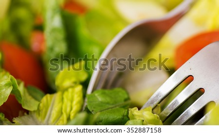 Closeup image of a fresh salad with forks. - stock photo