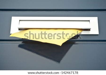 Closeup image of a front door built-in mailbox with a yellow parcel or letter partially in it. - stock photo