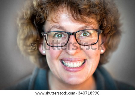 Closeup image of a laughing happy woman with glasses