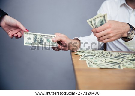 Closeup image of a male hand giving money to female hand - stock photo