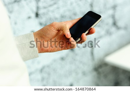 Closeup image of a male hand holding smartphone near the brick wall - stock photo