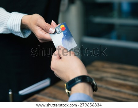 Closeup image of a man paying with credit card at the restaurant - stock photo