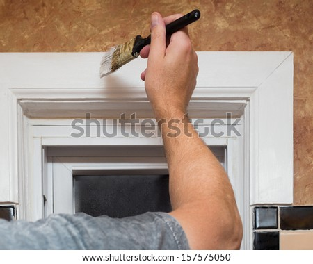 Closeup image of a mans hand with paintbrush while painting window trim - stock photo