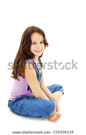 Closeup image of a pretty little girl sitting on the floor in jeans. Isolated on white background