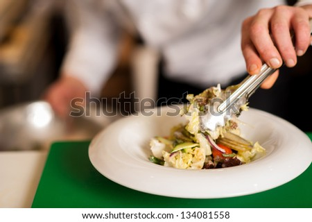 Closeup image of a salad ready to be served being decorated by chef. - stock photo