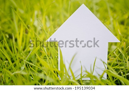 Closeup image of a white paper cutout house among fresh and green spring grass with copy space on the side. - stock photo