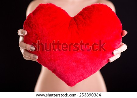 Closeup image of a woman holding red heart over black background - stock photo