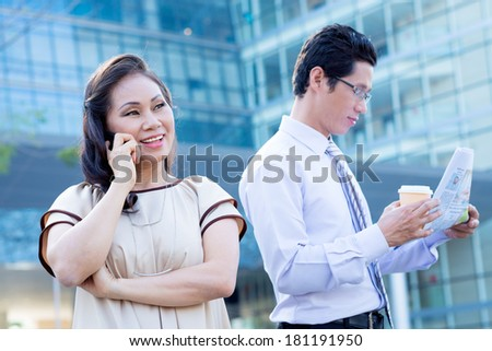 Closeup image of a woman talking by cellular while a businessman reading newspaper with coffee on the foreground  - stock photo