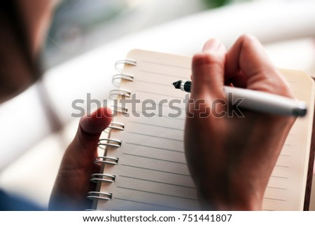 Closeup image of a woman writing and taking note on notebook with pen