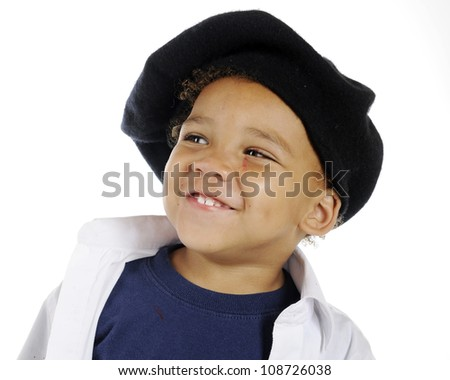 Closeup image of an adorable preschool artist happily wearing his French beret and white smock with bits of red paint splattered on his face.  On a white background. - stock photo