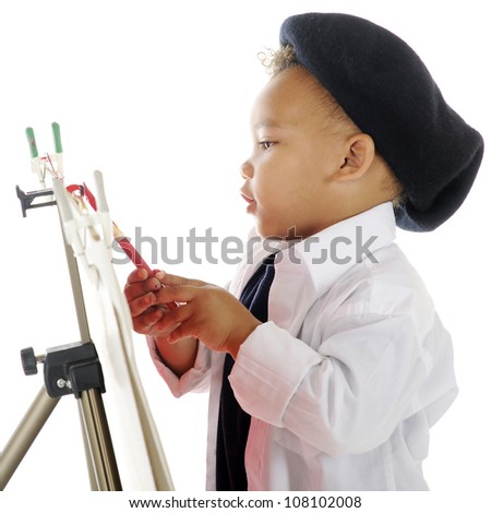 Closeup image of an adorable preschool artist painting on an easel in his smock and French beret.  On a white background. - stock photo