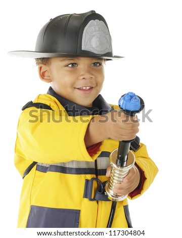 "Closeup image of an adorable preschool ""Fire Chief"" aiming at a (pretend) fire with his water hose.  On a white background."