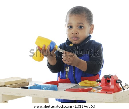 Closeup image of an adorable toddler playing carpenter with plastic tools on a work bench.  On a white background. - stock photo