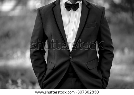 Closeup image of black and white half length body portrait of man wear a tuxedo with both hand in pocket on outdoor background location, wedding and business concept - stock photo