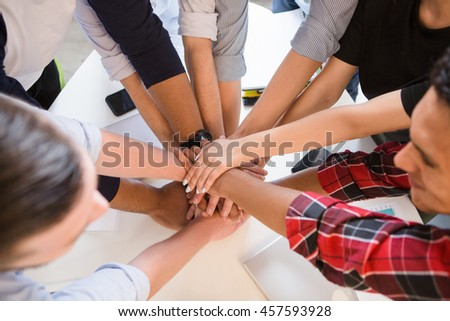 Closeup image of business people showing teamwork in office. Happy people smiling and having round table in board room.