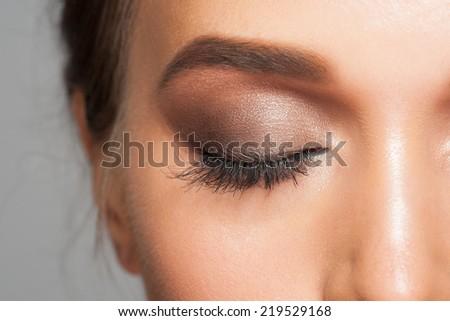 Closeup image of closed woman eye with beautiful bright makeup, smoky eyes - stock photo