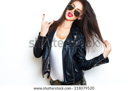 Closeup image of cool woman,showing her tongue,wear aviator sunglasses,fashionable outfit,hipster woman,stylish girl,rock sign,leather jacket,red lips,hiking woman,military jeans,amazing long hairs - stock photo
