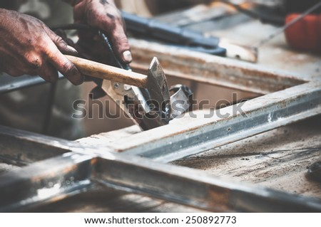 Closeup image of dirty worker hands doing hammer work on construction site