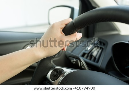 Closeup image of female hand holding car steering wheel - stock photo