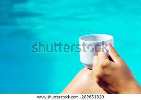 Closeup image of female holding cup of coffee near swimming pool - stock photo
