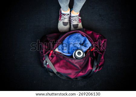 Closeup image of fitness bag with female legs - stock photo