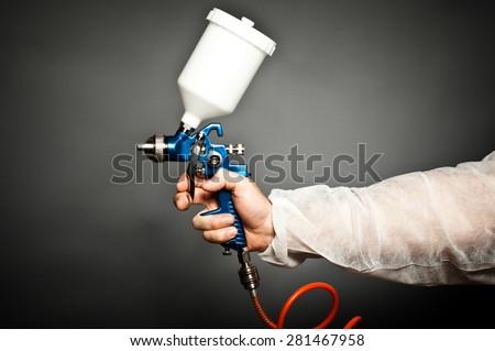 closeup image of hand hold spray gun - stock photo