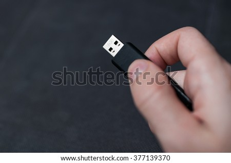 Closeup image of hand holding black USB data storage