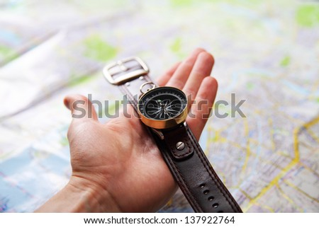 Closeup image of hand with magnetic compass over a map - stock photo