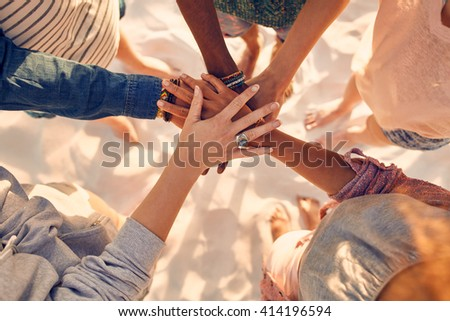 Closeup image of hands of young people with on stack. Group of mixed race friends on the beach with their hands stacked. - stock photo