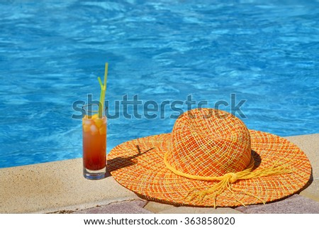 Closeup image of hat and cocktail at swimming pool, summer vacation concept