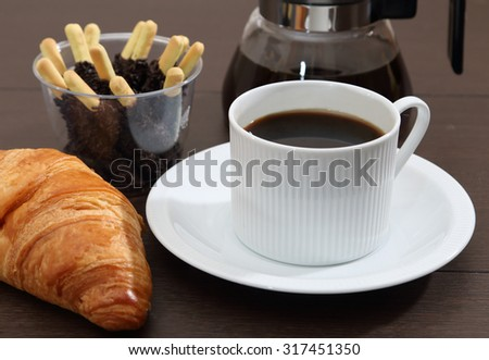 closeup image of hot black coffee and pie on table in the morning