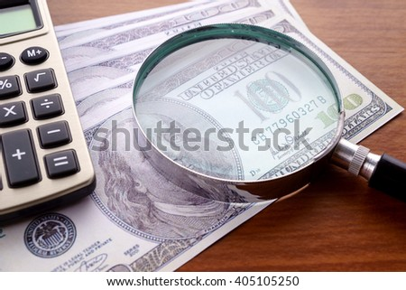 Closeup image of magnifying glass on hundred dollar bills with a calculator on wooden table. - stock photo